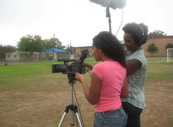 Picture of young woman filming. An older woman stands beside her, giving advice.